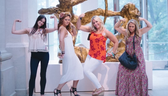 Four millennial women posing for a fun photo at the museum.